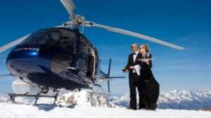 helicopter and young couple at the mountain top