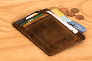 Wallet with card and coins on a desk