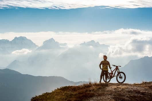 Man with bike on the mountain