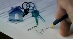 Man's hand signing a signuature with keys on the document