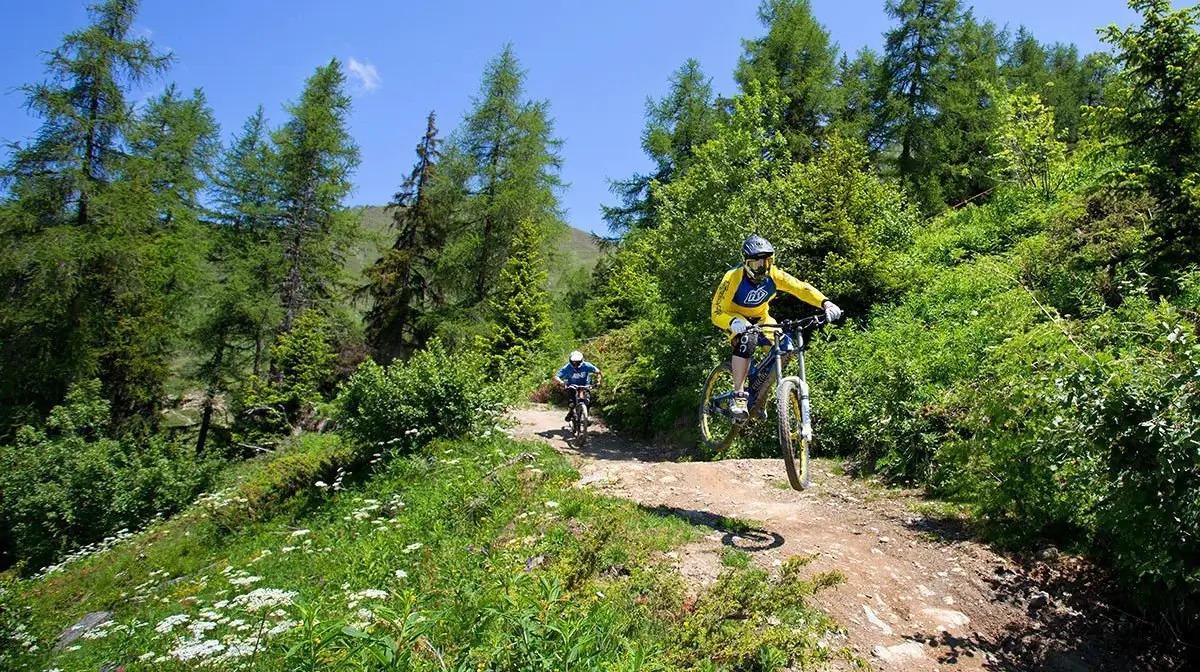 Two men riding bikes in a mountain