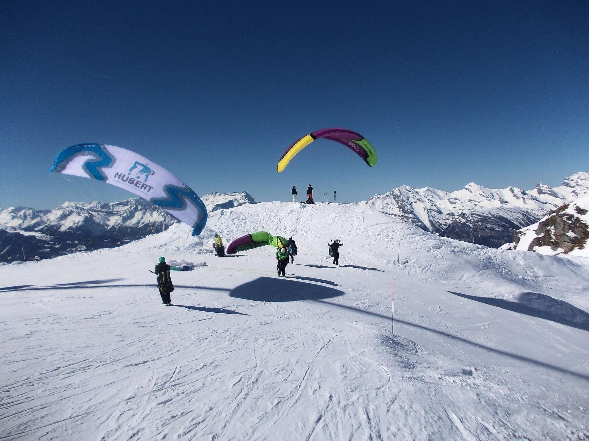People landing on a snowy mountain after paragliding in switzerland